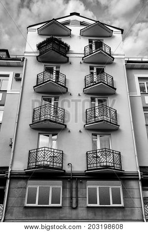 Vertical monochrome shot of six-story building with wrought iron balconies on sky background