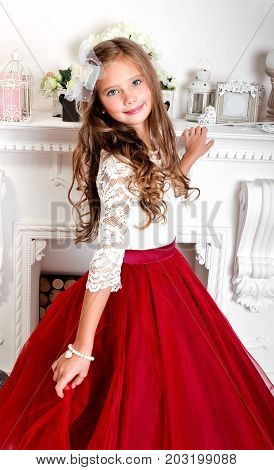 Adorable smiling little girl child in princess dress near the fireplace