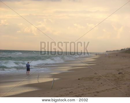 lone beach fisherman on the Atlantic coast of Florida at sunrise poster