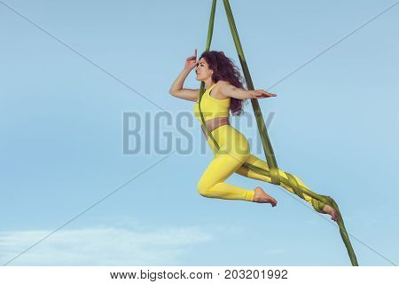 Woman the equilibrist highly in the sky during execution of a trick.