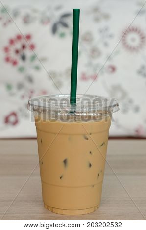 Iced latte coffee with green straw put on table and beautiful background.