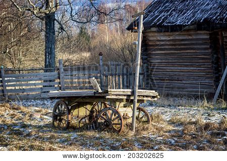 An old wooden cart stands on snow-covered grass.