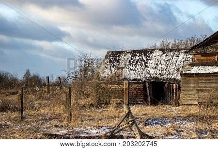 Sunny winter landscape with abandoned houses in the village of Palcevo. Russia, Tver region, Bologovsky District.