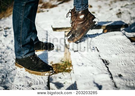 The young woman stand on tiptoe in front of the boyfriend. View of the legs of a couple in love. A date in winter at sunshine day outdoor. Lifestyle moments