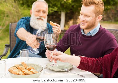 parents and adult son clinking glasses of wine while having dinner together