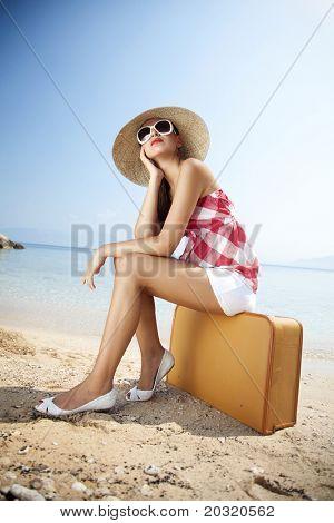 junge weibliche gestylten in 50er Jahre Sommer-Outfit auf einem retro Koffer am Strand sitzen