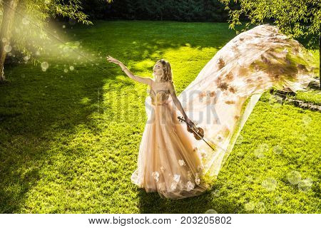 Beautiful fairy girl playing the violin on a sunny glade in the park. Musical concept. Classical music, violin.