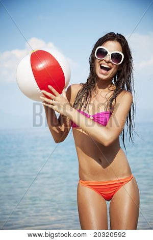 young female at the beach playing ball