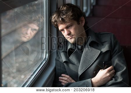 Traveling by train. Sad man traveling by train, looking through the window and thinking about unrequited love squeezing the phone in his hand. alone in an empty train wagon. Real people series. Toned picture.
