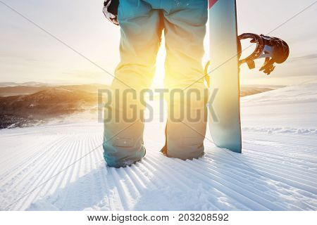 Closeup snowboarding concept. Girl snowboarder holding snowboard on ski slope at sunrise or sunset time