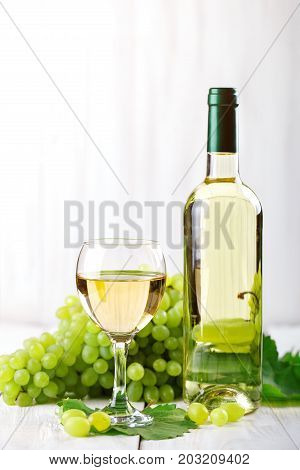 A glass of white wine, fresh grapes and a bottle of white wine on white wooden table.