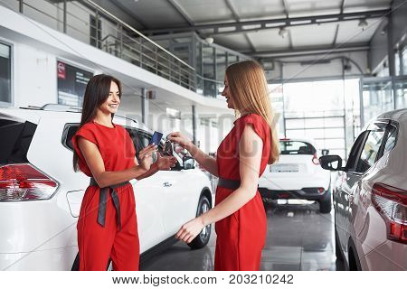 auto business, car sale, deal, gesture and people concept - close up of dealer giving key to new owner in auto show or salon.