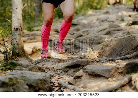 girl runner running rocks in bright crimson compression socks