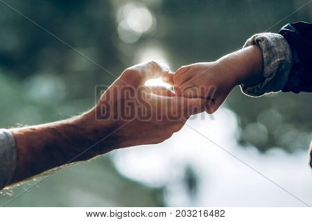 Father And Little Son Holding Hands In Summer Sun Light. Father Hand Lead His Child In  Nature Outdo
