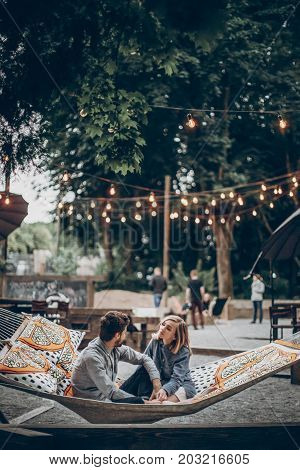 Stylish Hipster Couple Family Cuddling And Relaxing In Hammock Under Retro Lights In Evening Summer