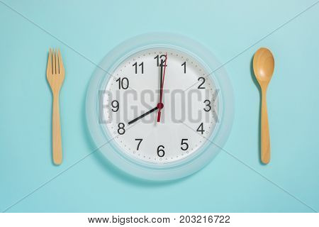 Flat Lay Of Meal Time, Wall Clock Spoon And Fork On Pastel Blue Color.