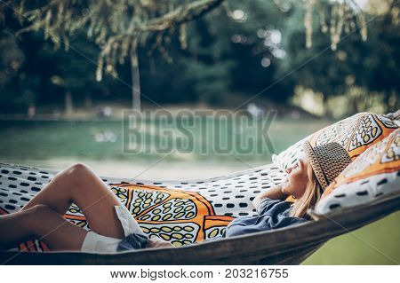 Stylish Hipster Woman Relaxing In Hammock In Sunny Summer Park. Travel And Wanderlust Concept. Blond
