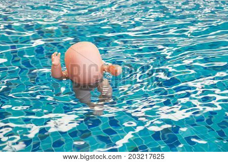 Baby Doll Floating In A Swimming Pool, The Dangers Of Children Drowning.