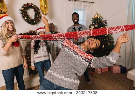 multiethnic friends playing limbo game while celebrating christmas together
