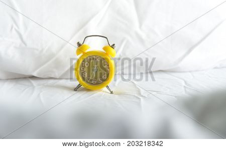 Yellow Alarm clock on bed in morning with sun light