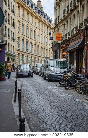 Paris,  France - June 3, 2017: Narrow cobblestone street Fosses-Saint-Jacques sandwiched by typical Parisian buildings. Black car moves slowly down on the street under overcast sky.