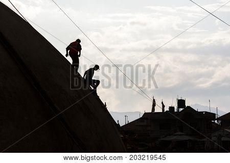 KATHMANDU NEPAL - 9/23/2015: Laborers descend the Boudhanath Stupa during post earthquake repairs in Kathmandu Nepal.