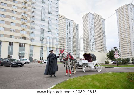 Coachman in cloak stands near couch with horse near residential buildings