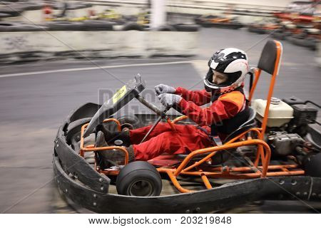 Girl in helmet drives in go-kart on track during competition, motion blur