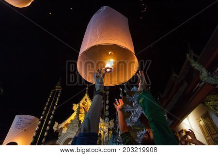 CHIANG MAI THAILAND - 12/30/2015: A group of tourists release floating lanterns at a Buddhist temple on New Year's Eve in Chiang Mai Thailand.