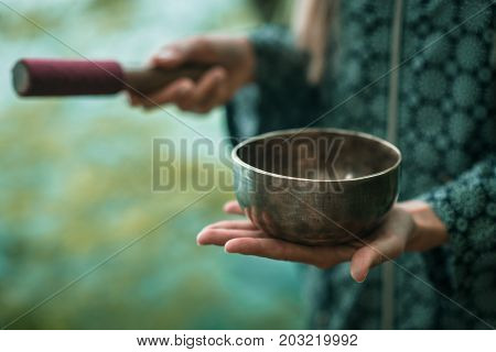 Singing Bowl ,  One Woman Only, Toned Image, Outdoors By The Lake,