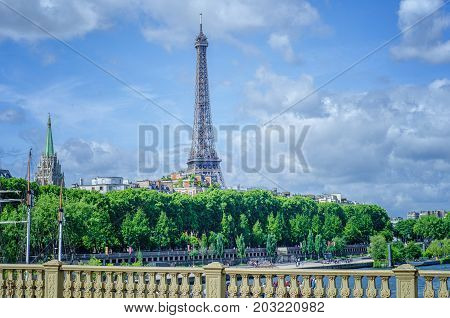 Paris,  France - June 4, 2017: The view of Eiffel Tower and American Church green spire from the Invalides bridge