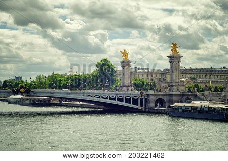 Paris,  France - June 4, 2017: Bridge Alexandre III with two gilded statues Fames in summer rainy day