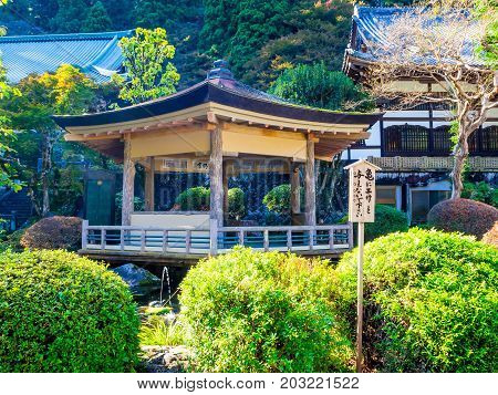 Nara, Japan - July 26, 2017: Unidentified people sitting inside of a building in the garden, enjoying the pond at Todai Ji Temple.