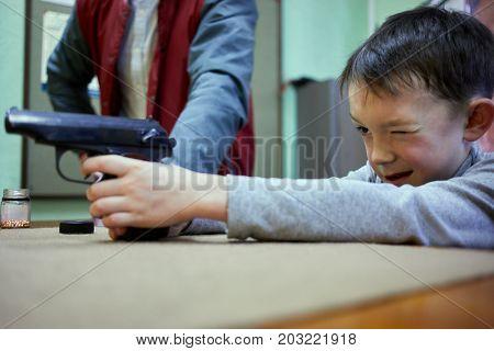 Little boy aims pistol in shooting gallery.
