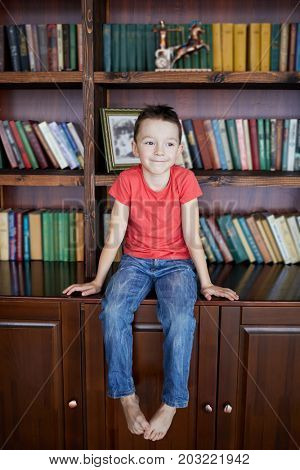 Little barefoot boy sits on bookcase with books.