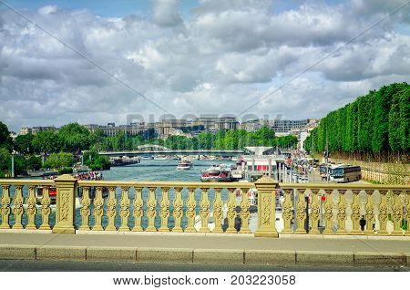 Paris,  France - June 4, 2017: View of Seine with moving tourist cruise boats was shot from Invalides bridge. In the right side there are Jardin d'Erevan and coaches nearby Bateaux-Mouches boat tour agency