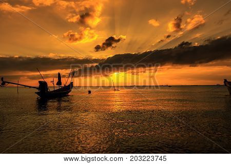 Dramatic Sunset with silhouette local boat in Thailand