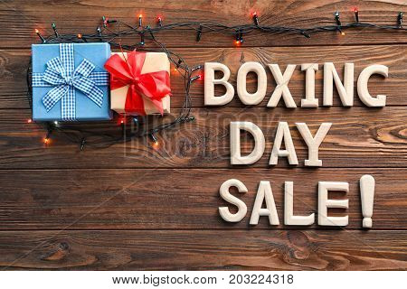 Text BOXING DAY SALE and gift boxes on wooden background