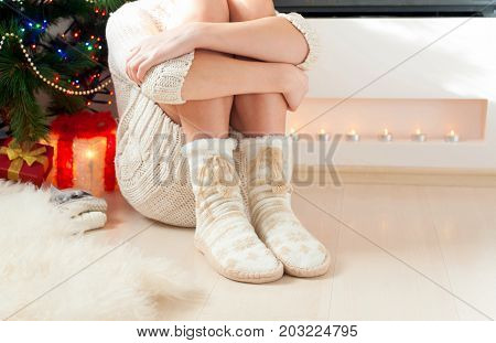 Young girl arms hugging legs in cozy warm woolen ornamental socks with pompons. Indoors.