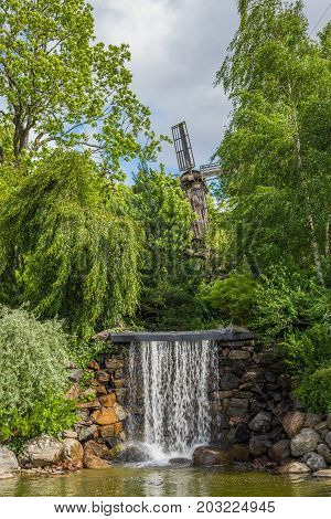 Small waterfall with stones and mill at the background.