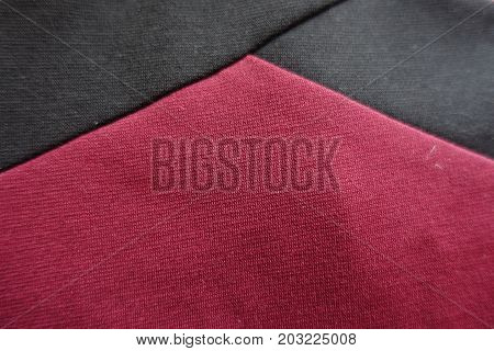 Angle Of Black Ribbons On Maroon Fabric