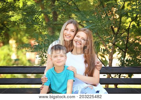 Lesbian couple with foster son in park. Adoption concept
