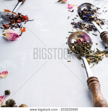 Background with assorted tea leaves, black, green, rooibos and strawberry in mesuring spoons. Healthy drink concept. Copy space.