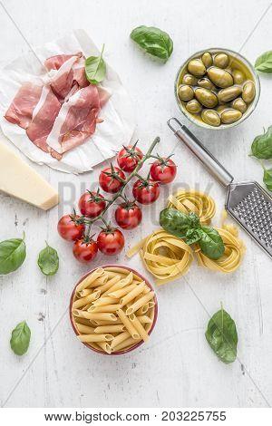 Italian Or Mediterranean Food Cuisine And Ingredients On White Concrete Table. Tagliatelle Pene Past
