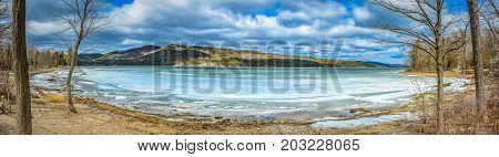 Panoramic winter view of a lake with ice