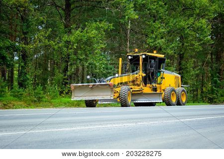 Yellow tractor bulldozer grader on the road