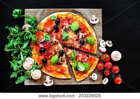 Pizza Margherita with cheese and basil leaf on dark background with fresh ingredients for you to design and restaurant menu. Delicious Homemade Cheese pizza