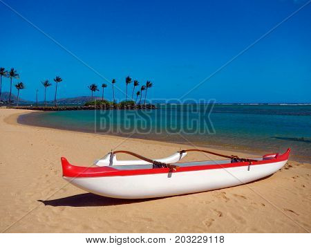 Red and white outrigger canoe on a sandy beach and blue sky in Hawaii