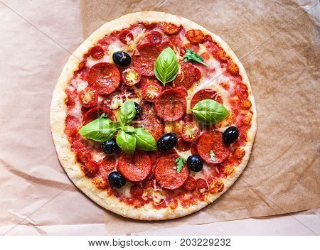 Pizza pepperoni with Ham Pepperoni and Bacon on baking craft paper background with fresh ingredients for you to design and restaurant menu. Delicious Homemade Meat pizza