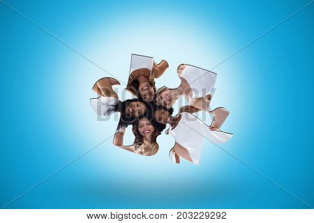 Happy women forming a huddle against blue background